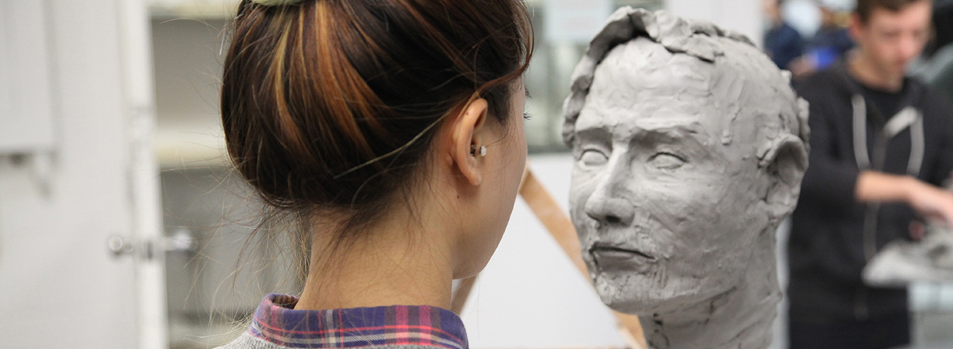 Photo of student sculpting a clay head